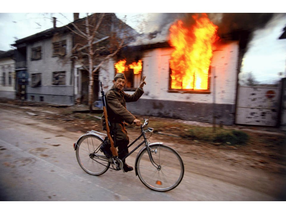 Blood and Honey: A Balkan War Journal Soldiers and Paramilitaries - A Serbian soldier cycles by a burning house on the destroyed streets of Croatian city of Vukovar, Nov. 24, 1991. ronhaviv.com
